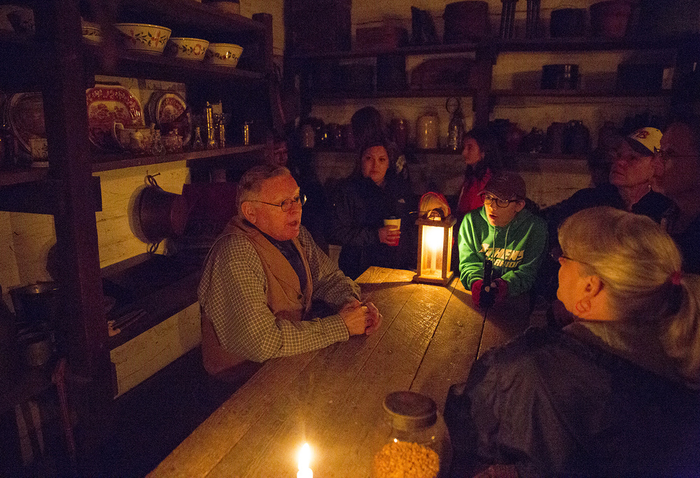 John Blankenberger visits with people who stopped in the Sam Hill grocery store during the annual Candlelight Walk at New Salem State Historic Site Friday, Oct. 2, 2015. Rich Saal/The State Journal-Register