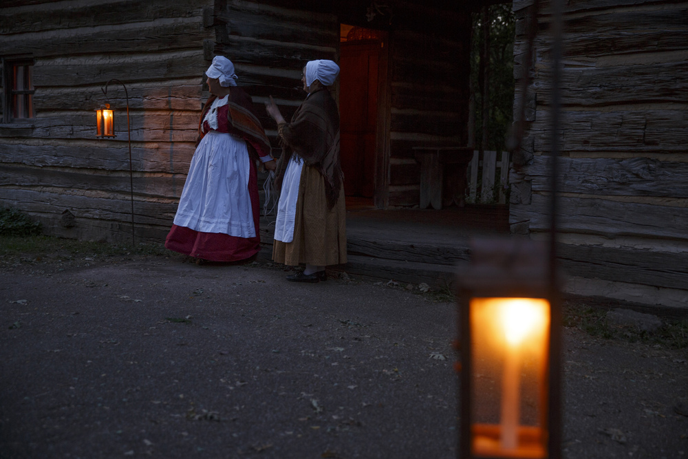 Rebecca Look, left, and Linda Flotow watch from the porch of the Kelso-Miller house as visitors arrive for the annual Candlelight Walk at New Salem State Historic Site Friday, Oct. 2, 2015. Rich Saal/The State Journal-Register