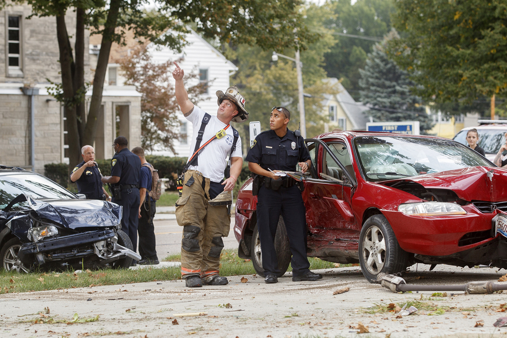 A Springfield Firefighter shows a Springfield Police officer a leaning power pole at the intersection of South Pasfield Street and South Grand Avenue after a two car accident Monday, Sept. 28, 2015. One person was hospitalized. Ted Schurter/The State Journal-Register