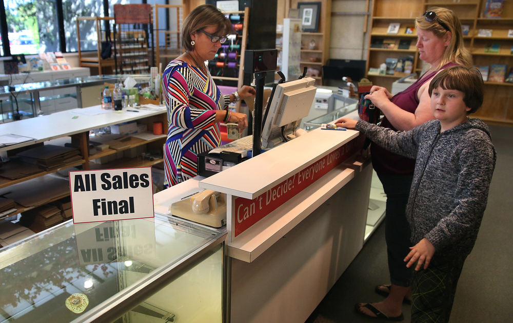 "A sale in the museum's gift shop since last Tuesday has emptied shelves of most items. Employee Pam Goetz rings up a sale for Waggoner resident Cynthia Pedigo, who said she visits the museum at least four times a month and visited Wednesday with son Billee Gratton, 9 at right as well as her two other sons. The 138-year-old Illinois State Museum in Springfield is scheduled to close to the public at the end of the day on Wednesday, Sept. 30, 2015. The closure is due to the state's budget crisis, even though most staff will still report to work and the museum's board chairman says the savings will amount to ""peanuts"" according to a story by the Associated Press. David Spencer/The State Journal-Register"