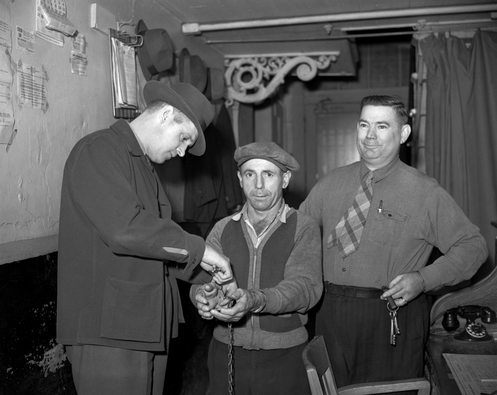 John Joseph Miller, murder suspect, in handcuffs at Sangamon County jail with Deputy Jack Armstrong, left, and jailer Jess Cowie October 20, 1941.Miller was being taken to the state's attorney's office for questioning in a 16-year-old murder case. File/The State Journal-Register