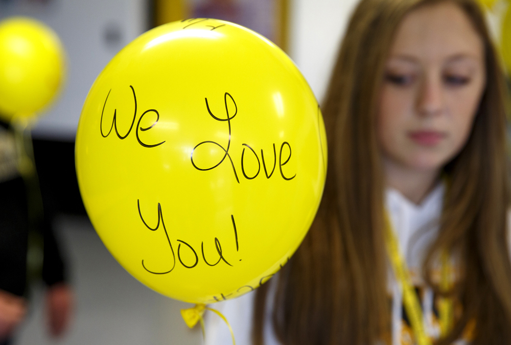Sidney Donnan personalized her balloon before the launch to honor Robert Sanders, the A-C Central Middle and High School principal who died Wednesday. A remembrance ceremony and balloon launch was held at the school Friday, Oct. 9, 2015 in Ashland. Rich Saal/The State Journal-Register