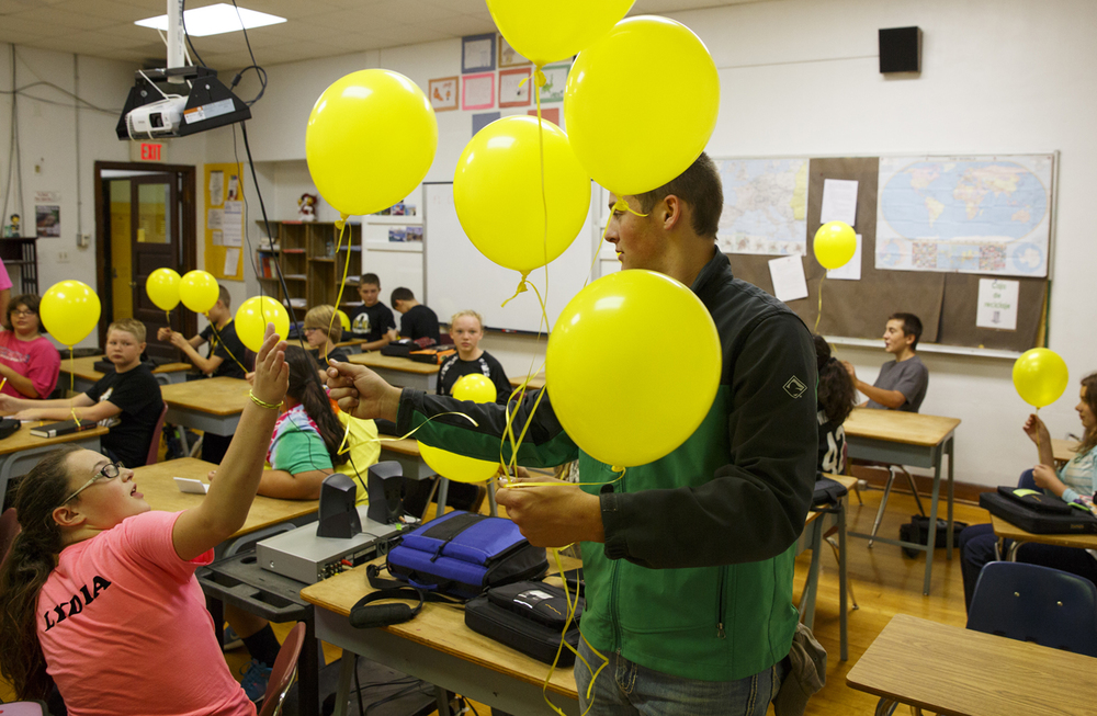 Jackson Allen passes out balloons to a seventh grade class at A-C Central Middle and High School Friday, Oct. 9, 2015. The schools held a remembrance ceremony and balloon launch to honor Robert Sanders, the schools' principal who died Wednesday. Rich Saal/The State Journal-Register