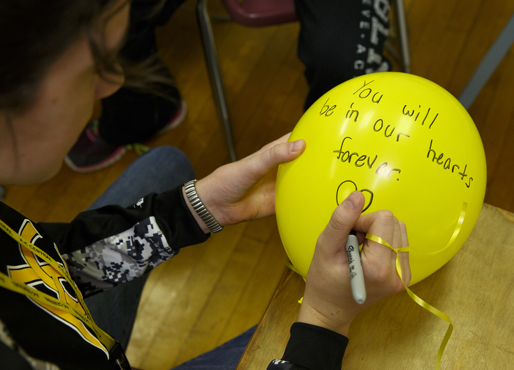 Bailey Eilers writes a message on a balloon at A-C Central Middle and High School Friday, Oct. 9, 2015. The schools held a remembrance ceremony and balloon launch to honor Robert Sanders, the schools' principal who died Wednesday. Rich Saal/The State Journal-Register