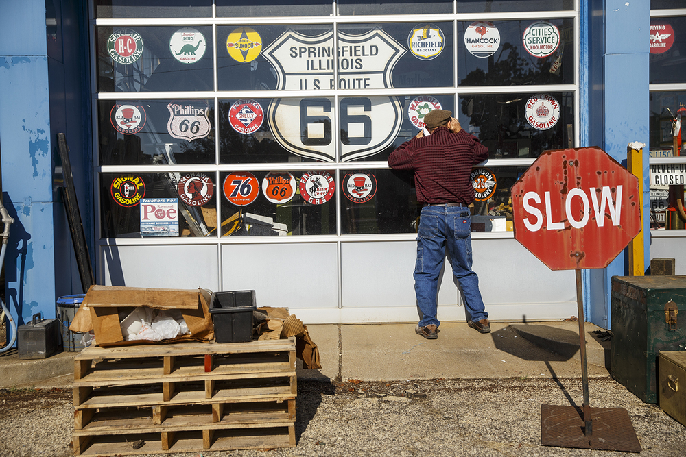 Tom McCloskey peers through the service door at Shea's Gas Station and Museum in Springfield Saturday, Oct. 10, 2015. Although the two main buildings were closed, the contents stored outside the main buildings were auctioned off, including dozens of truck toppers, miscellaneous tools and parts,  a school bus and an Airstream Cruiser. Ted Schurter/The State Journal-Register