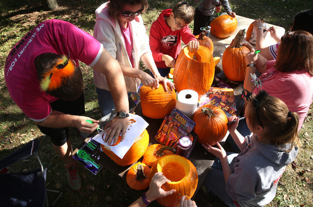 The Brown family of Girard, who said they have been coming to the event for the past eight or nine years, took over a picnic table, carving multiple pumpkins together. David Spencer/The State Journal-Register