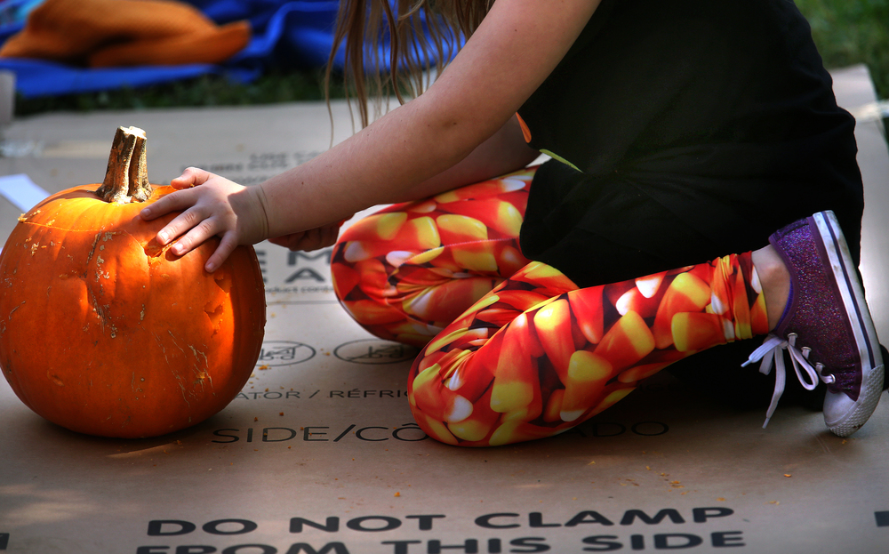 The Halloween fashion theme continued by some of those attending this year's carving event, with nine-year-old Tori Vizral's leggings showing off candy corn as she carved a pumpkin with dad Michael Vizral and brother Isaac Vizral. David Spencer/The State Journal-Register