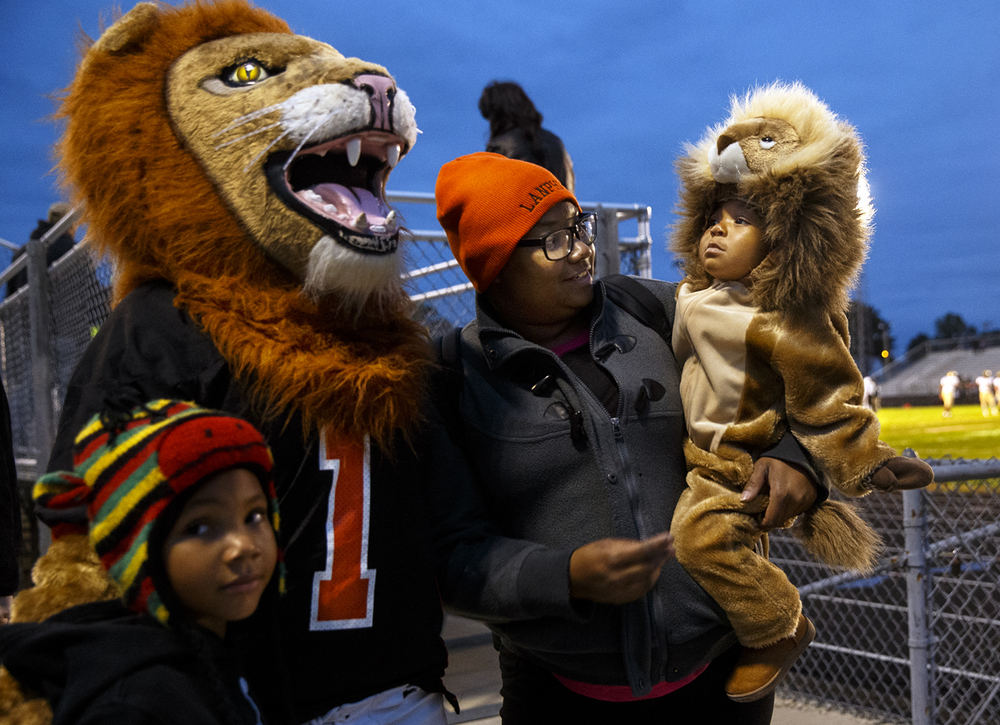 Destiny Higgerson's daughter Phoenix glances at Leo, the Lanphier Lion's mascot before taking in the game against Sacred Heart-Griffin Friday, Oct. 9, 2015. Ted Schurter/The State Journal-Register