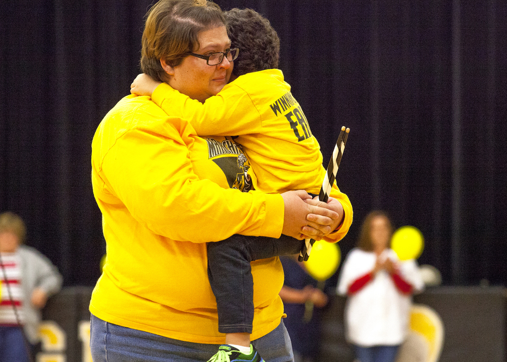 Robert Sanders' daughter, Laura Williams, holds her son, Devon, after he had been presented with a pair of drumsticks from the school band's drum line, during a remembrance ceremony at A-C Central Middle and High School Friday, Oct. 9, 2015 in Ashland. Sanders, the school's principal, died Wednesday. Rich Saal/The State Journal-Register