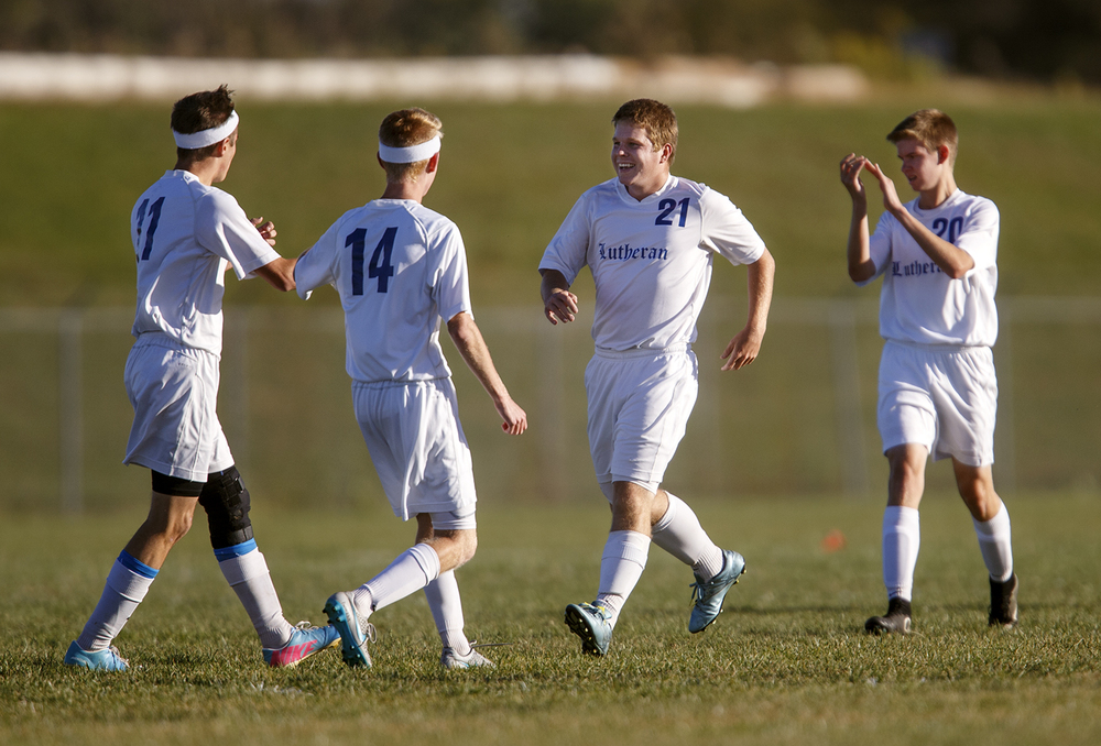 Lutheran's Jeremiah Sausaman (21) is congratulated by his teammates after scoring against North Mac during the Class 1A Riverton Regional Tuesday, Oct. 13, 2015. Ted Schurter/The State Journal-Register