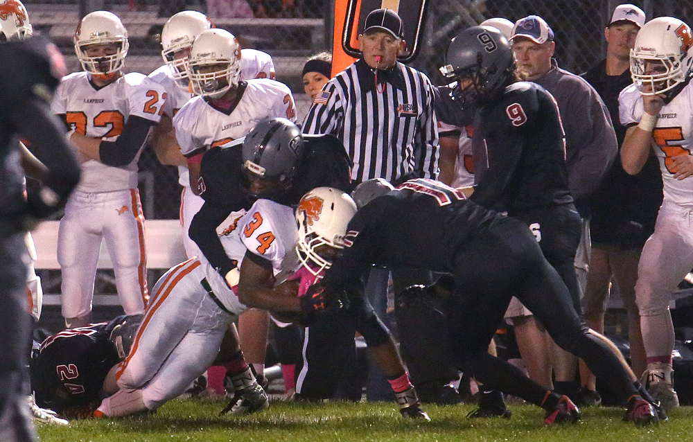 Lanphier ball carrier JacAnthony Childress is brought down by a trio of Senator defenders including Dee Kalala at left, Davonte Day at middle and Peyton West at right. David Spencer/The State Journal-Register