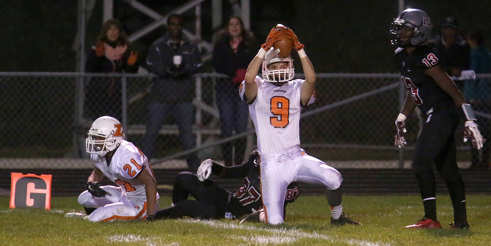 Lanphier defender Elijah Forshee holds up the ball near the goal line after intercepting it with the help of teammate Cameron Smith at far left in a play involving Springfield receiver Cameron Jones.  David Spencer/The State Journal-Register