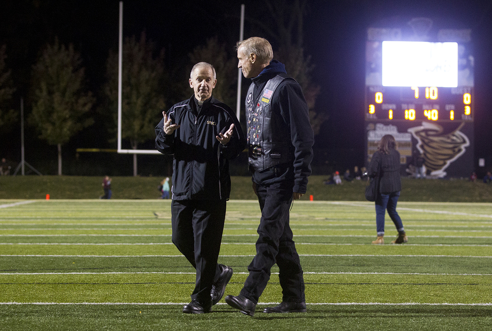 Bishop Thomas John Paprocki of the Diocese of Springfield visits with Illinois Gov. Bruce Rauner before the start of the Sacred Heart-Griffin Southeast game at Sacred Heart-Griffin Friday, Oct. 16, 2015. Ted Schurter/The State Journal-Register
