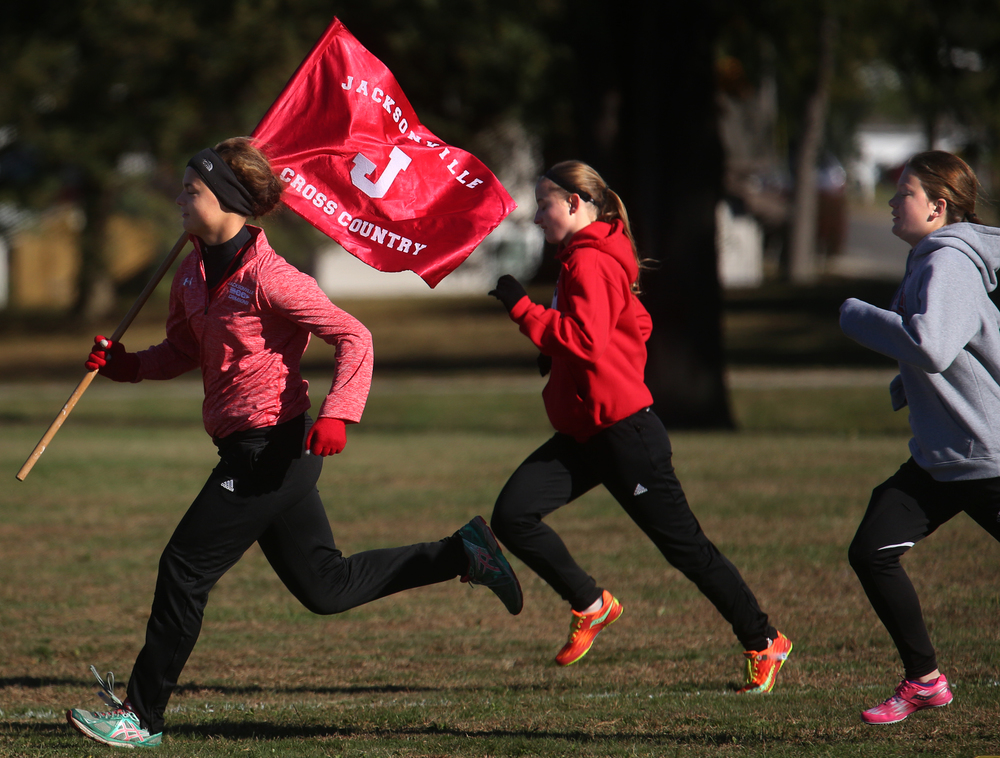 Members of the Jacksonville High School girls team do sprints before the start of their race. David Spencer/The State Journal-Register