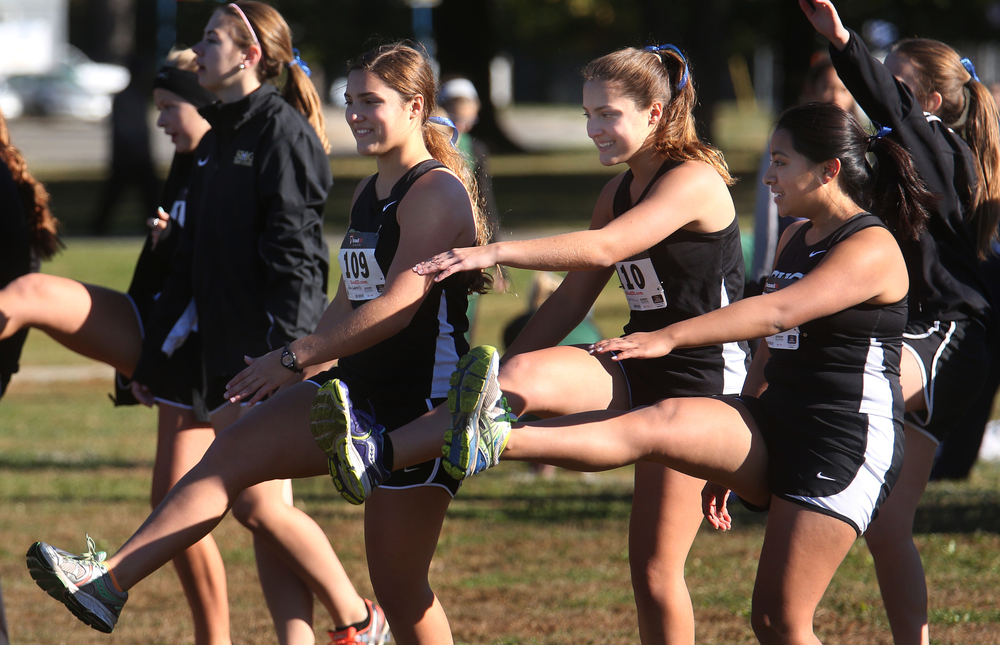 Members of the Sacred Heart Griffin girls team do some high-kick leg stretches before the start of their race at the starting line. David Spencer/The State Journal-Register