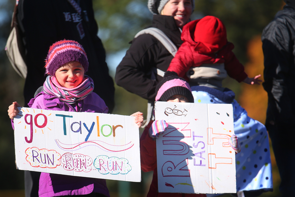 Near the start line and bundled up, young cheerleaders MaeLynn Smith at left and sister Kinlee Smith held signs supporting runner Taylor Justison of the Chatham Glenwood team. David Spencer/The State Journal-Register