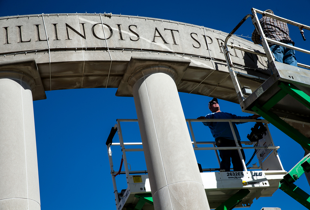 David Wells, left, and Jerrad Frank, right, both UIS maintenance electricians with IBEW Local 193, take advantage of the warm weather for October to get a head start on hanging holidays lights on the colonnade at the University of Illinois Springfield, Wednesday, Oct. 14, 2015, in Springfield, Ill. Justin L. Fowler/The State Journal-Register
