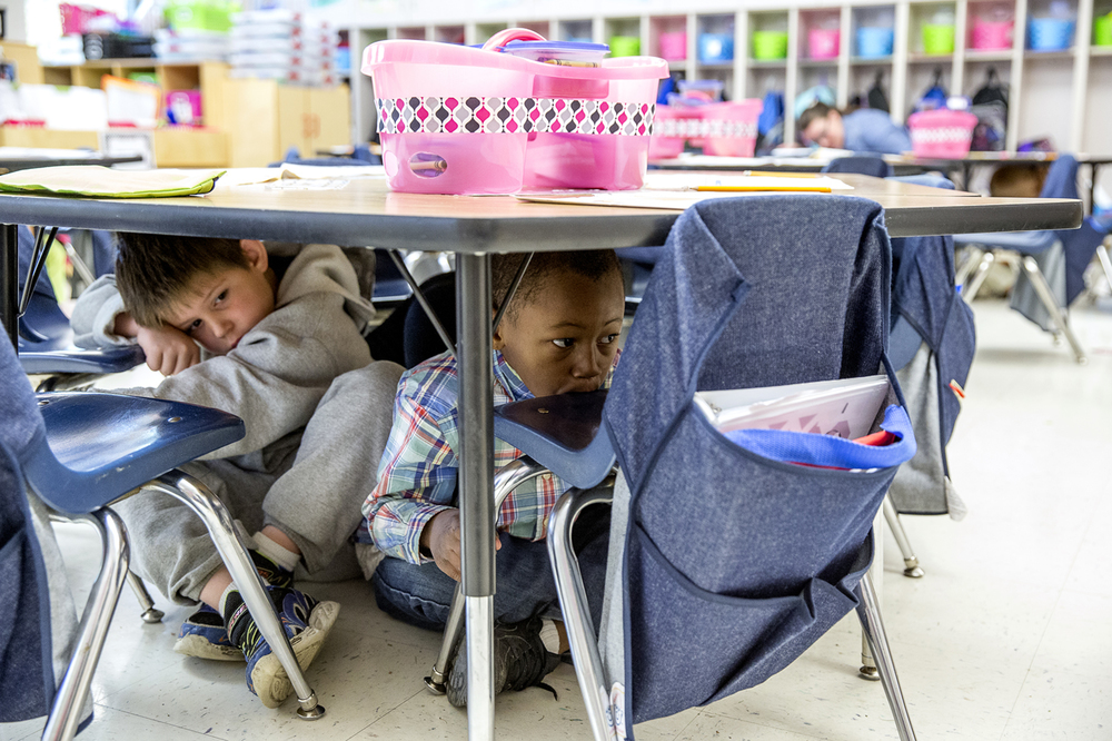 "First graders Mason Casper, left, and Herbert Blackman, center, huddle underneath their desk during the Great ShakeOut Earthquake Drill at Ridgley Elementary School,  Thursday, Oct. 15, 2015, in Springfield, Ill. The students learned what to do in an earthquake with the ""Drop, Cover, and Hold On"" drill during the nationwide event. It serves to educate the public on emergency practices and plans to keep them safe during an earthquake. Justin L. Fowler/The State Journal-Register"