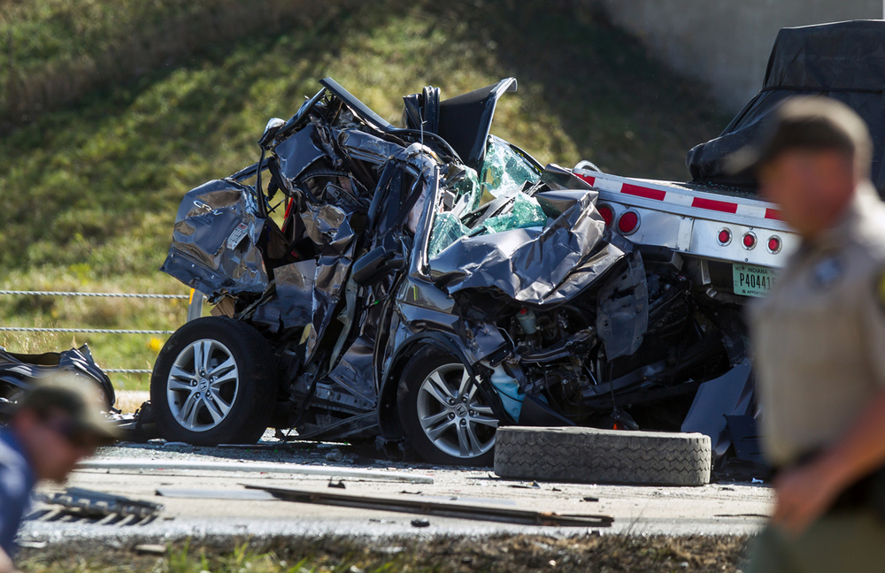 A Honda passenger vehicle sits crumpled with its front end lodged underneath the trailer of a semi after a multiple vehicle accident on the southbound lanes of Interstate 55 north of the West Pulliam Road overpass, Thursday, Oct. 15, 2015, south of Chatham, Ill. Justin L. Fowler/The State Journal-Register