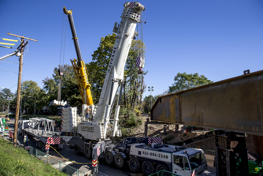 Crews begin removing the counterweights on a massive crane used to place the steel walls on the new replacement bridge for the Ninth Street overpass, Friday, Oct. 16, 2015, in Springfield, Ill. The replacement bridge will be put in place during the closure of the Third Street rail corridor from Oct. 17 to Oct. 31. Justin L. Fowler/The State Journal-Register