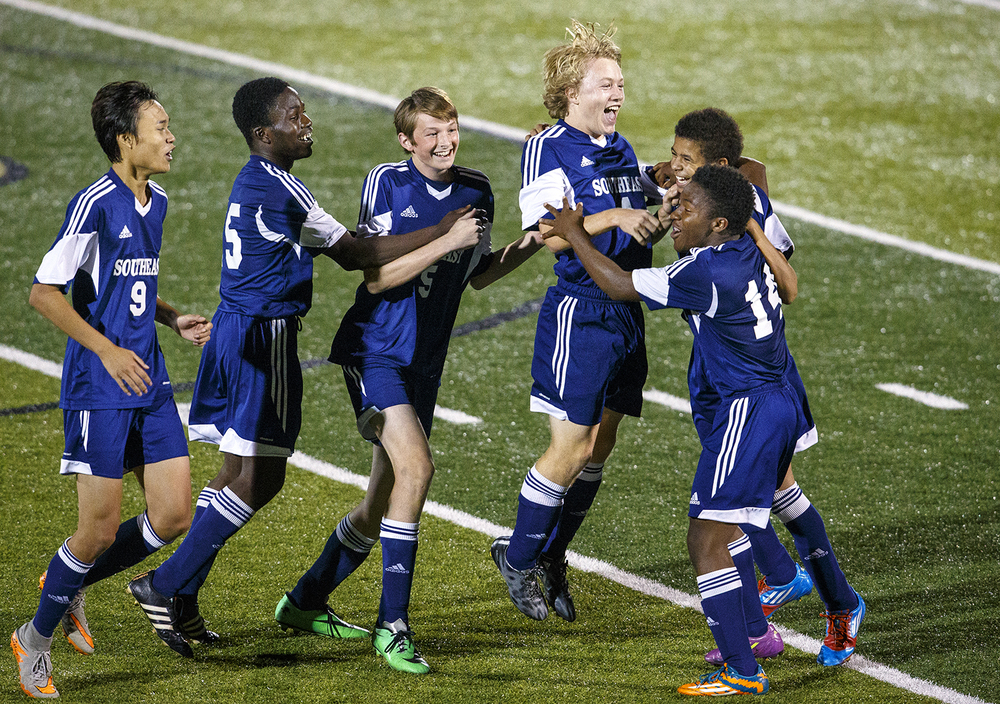 Southeast's Zach McVey leaps into the air as he is mobbed by his teammates at the conclusion of the Spartans 1-0 upset win against Sacred Heart-Griffin during the Class 2A Sacred Heart-Griffin Regional semifinals Wednesday, Oct. 21, 2015. McVey scored the game's only goal. Ted Schurter/The State Journal-Register