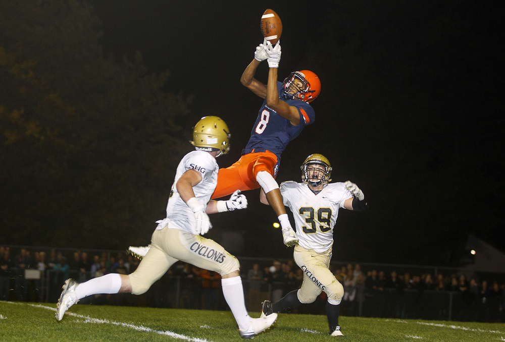 Rochester's Collin Stallworth leaps for a pass under pressure from Sacred Heart-Griffin defenders at Rochester High School Friday, Oct. 23, 2015. Ted Schurter/The State Journal-Register