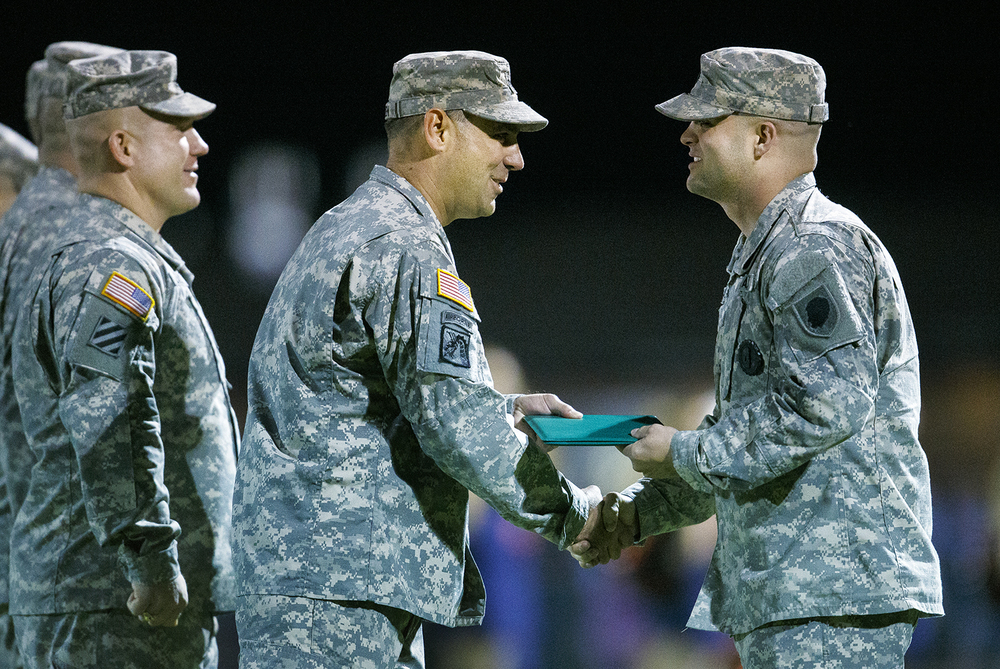 Illinois Army National Guard Colonel Daniel Reichen shakes hands with Justin Angel of Rochester after promoting him to Staff Sergent during a ceremony before the Rochester Sacred Heart-Griffin football game Friday, Oct. 23, 2015. Angel was promoted after being recognized as the number one recruiter in the state. Ted Schurter/The State Journal-Register
