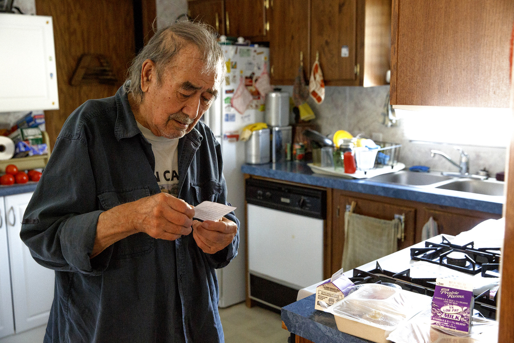 Antonio Ramirez reads a note at his home Thursday, Oct. 22, 2015 that was attached to his delivery from the Daily Bread program announcing delivery on Fridays will stop beginning November 6. The move is because of state budget cuts to Senior Services of Central Illinois, which administers the program. Ramirez, 94, and his disabled son receive meals each week day. Rich Saal/The State Journal-Register