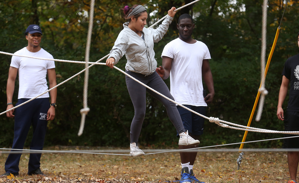 "On the ""P-Star"" challenge, a series of elevated ropes and cables in which participants navigate similar to walking on a tightrope, student Diana Quintero makes here way on a cable with the assistance of a fellow student as well as holding onto two suspended guide ropes. University of Illinois Springfield freshman enrolled in the STARS (Students Transitioning for Academic Retention and Success ) program took on the UIS Challenge Course on the grounds of Spencer House, a university-owned home on West Lake Shore Drive on Friday, Oct. 23, 2015. The course features seven fixed ""initiatives"" or ""challenges"", and participants work as a team through problem solving and communication in order to master each challenge. David Spencer/The State Journal-Register"