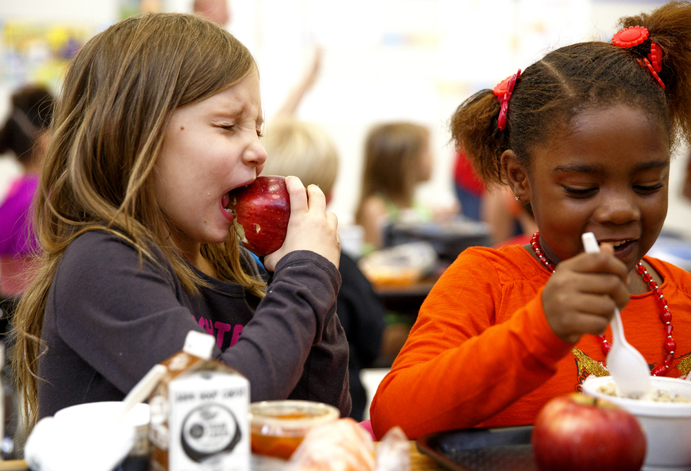 Missing teeth come with the territory when you're a first grader, but they would have come in handy for Brooklynn Dibler when she tried to bite into an apple Thursday, Oct. 22, 2015 during Illinois' Great Apple Crunch Day at Enos School. The event is a pilot program coordinated by the Illinois Farm to School Network, Agriculture in the Classroom and the Illinois Farm Bureau meant to promote local and healthy food in schools. The apples eaten by District 186 students were donated by Rendleman Orchards in Altopass. Nevaeh Brown, right, was eating the daily entree of hamburger stroganoff. Rich Saal/The State Journal-Register