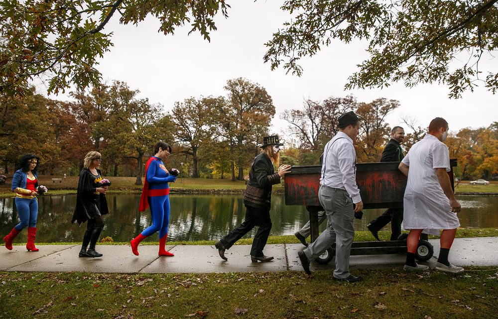 Accompanied by comic book character wedding attendants, Jake Bryant pushes his bride to be Amanda Jones in a casket toward their Halloween day wedding ceremony at the gazebo at Washington Park Saturday, October 31, 2015. Ted Schurter/The State Journal-Register