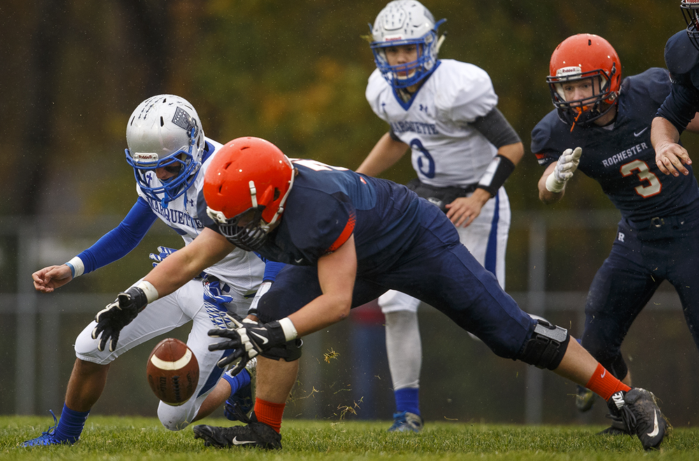 Alton Marquette's Brady Mcafee and Rochester's Evan Boxman dive for a loose ball in the first round of the Class 4A football playoffs at Rocket Booster Stadium Saturday, Oct. 31, 2015.  Ted Schurter/The State Journal-Register