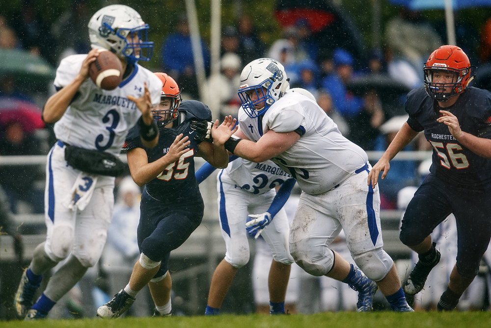 Rochester's Talon Williams (85) and Austin Mathis (56) push through the Alton Marquette defense to pressure quarterback Trey Aguirre in the first round of the Class 4A football playoffs at Rocket Booster Stadium Saturday, Oct. 31, 2015.  Ted Schurter/The State Journal-Register