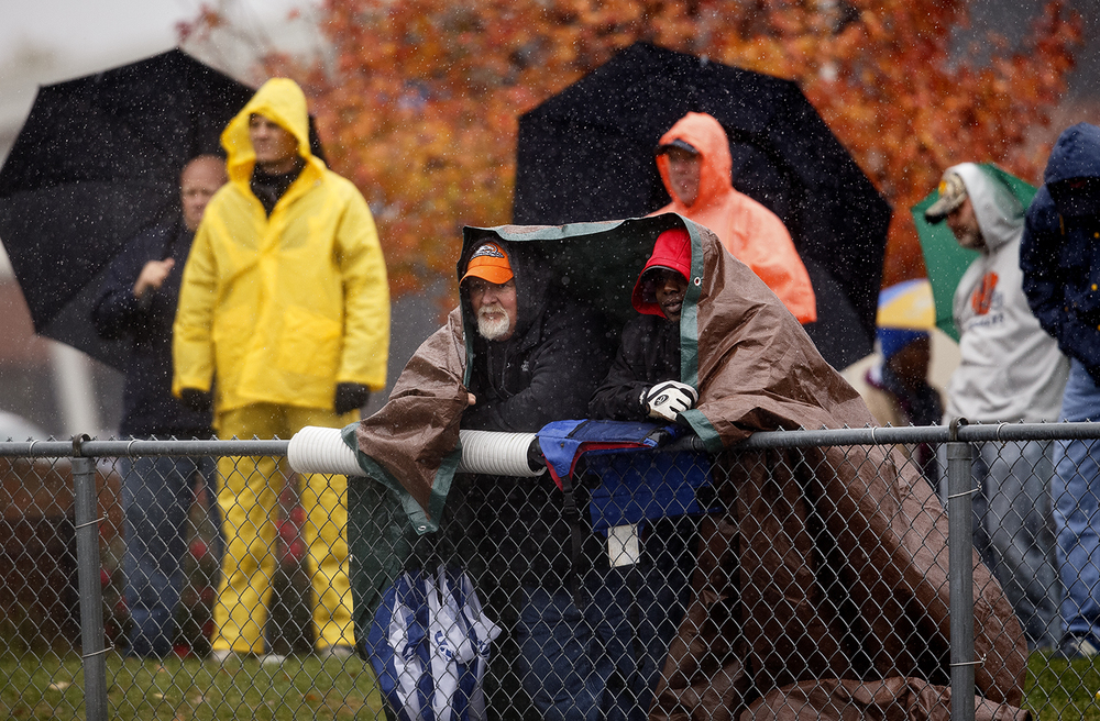 Fans endured persisten rain during the Rochester Alton Marquette game in the first round of the Class 4A football playoffs at Rocket Booster Stadium Saturday, Oct. 31, 2015.  Ted Schurter/The State Journal-Register