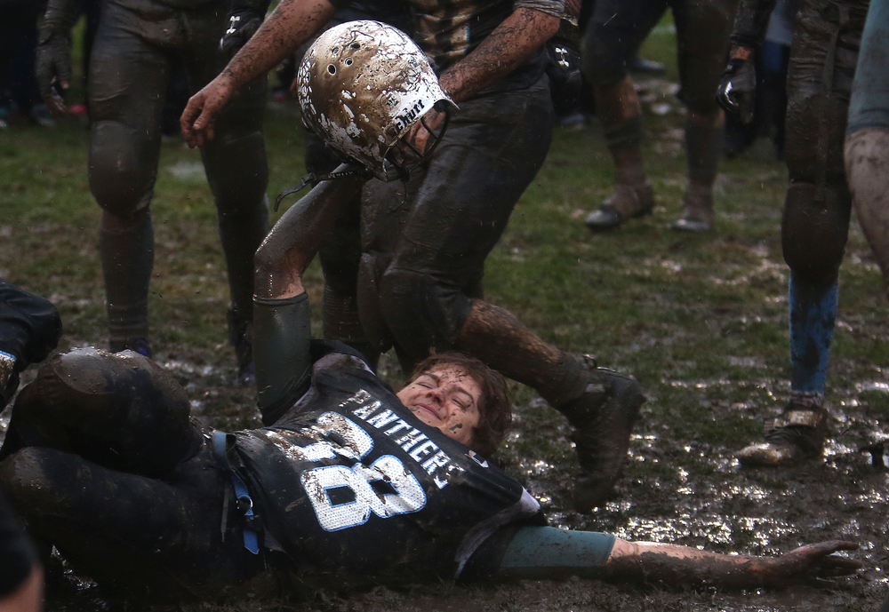 A North Mac player celebrates as he and teammates made it a mud bowl during their victory slide in the middle of the field at the end of the game. David Spencer/The State Journal-Register