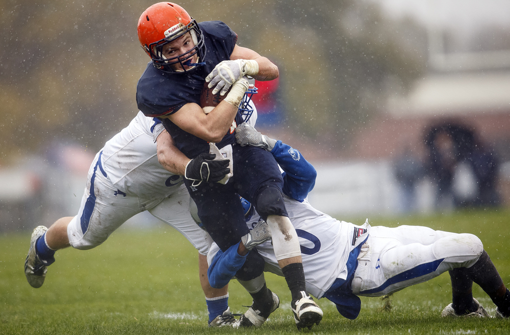 Rochester's Kenny Hedges plows forward as two Alton Marquett defenders drag him down in the first round of the Class 4A football playoffs at Rocket Booster Stadium Saturday, Oct. 31, 2015.  Ted Schurter/The State Journal-Register