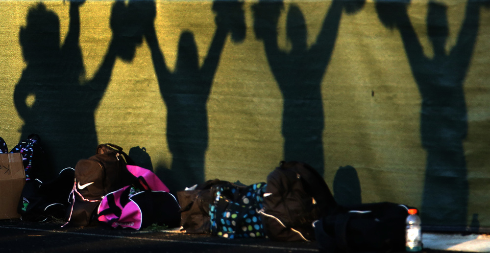 Silhoutted members of the Warrior cheerleading squad doing cheers celebrating a touchdown are seen against the front of the bleachers in late afternoon light at Knoles-Thompson Field.  David Spencer/The State Journal-Register