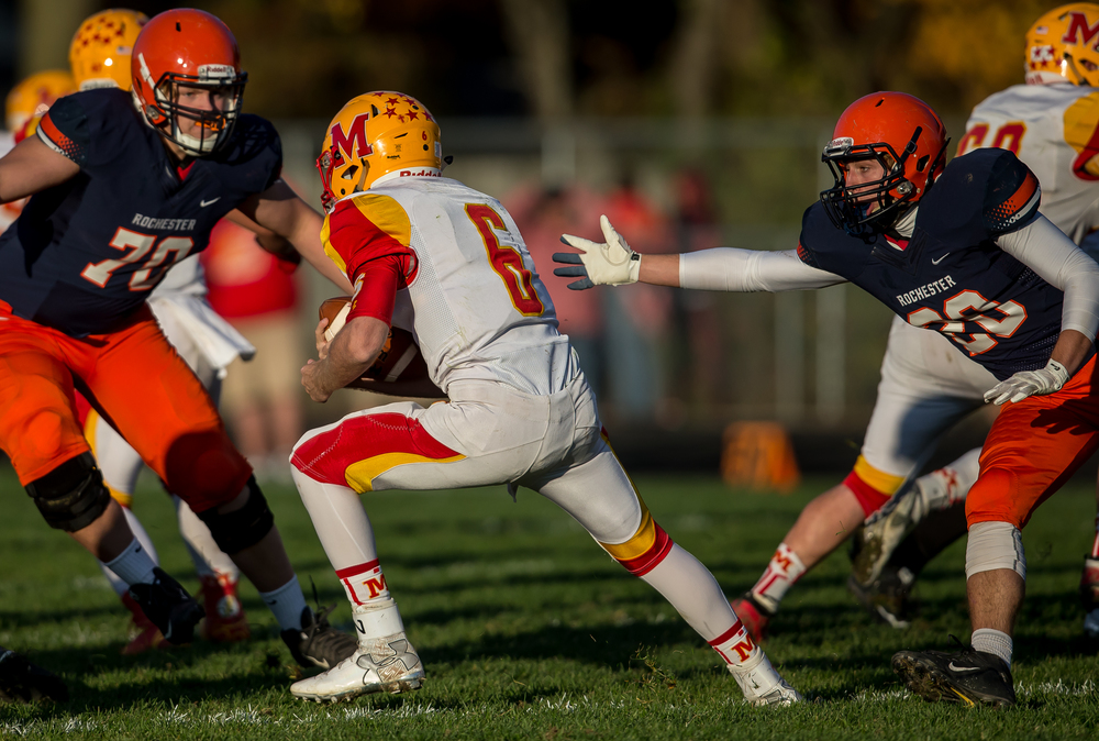 Murphysboro quarterback Braden Miller (6) evades the grasp of Rochester's Chase Kuntzman (20) on a rush in the second quarter during the second round of the Class 4A playoffs at Rochester High School, Saturday, Nov. 7, 2015, in Rochester, Ill. Justin L. Fowler/The State Journal-Register