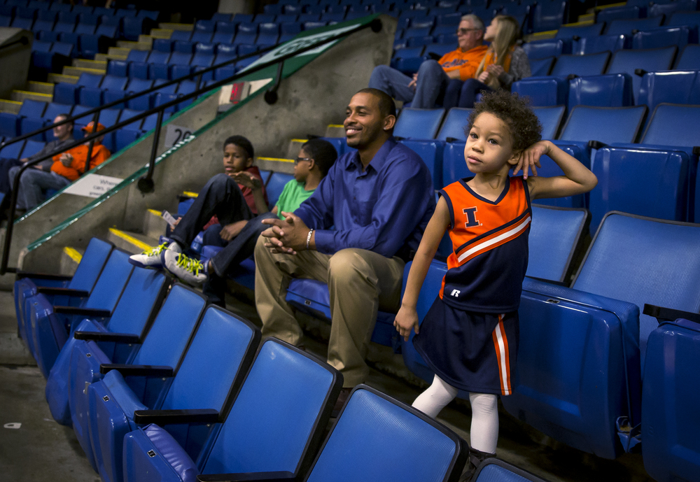 "Joy Bardwell, 3, dances along to the music playing over the loudspeakers as she gets ready to take in the game with her father, Jason Bardwell, left, and three brothers as the University of Illinois takes on the University of Illinois Springfield in an exhibition game at the Prairie Capital Convention Center, Sunday, Nov. 8, 2015, in Springfield, Ill. ""I haven't seen these guys since I was a kid,"" said Jason Bardwell of the opportunity to watch the Illini play at the PCCC. Justin L. Fowler/The State Journal-Register"