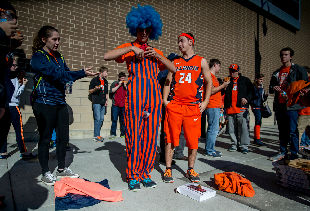 University of Illinois sophomore Matt Giddens, center, gets a speaker setup in his Illini themed coveralls as he has pizza with his fellow Orange Krush members prior to the University of Illinois vs. the University of Illinois Springfield exhibition game at the Prairie Capital Convention Center, Sunday, Nov. 8, 2015, in Springfield, Ill. Justin L. Fowler/The State Journal-Register