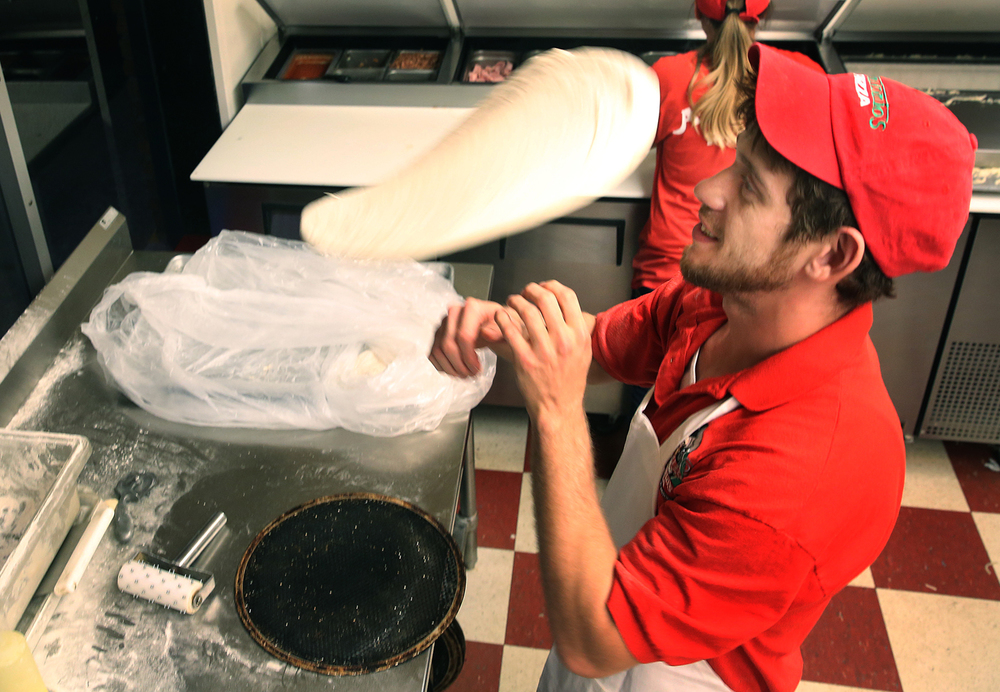 Antonio's Pizza employee Andrew Escobar sends pizza dough airborne while making a pie in the kitchen at Antonio's Wabash Ave. store in Springfield on Wednesday evening, Nov. 5, 2015. David Spencer/The State Journal-Register