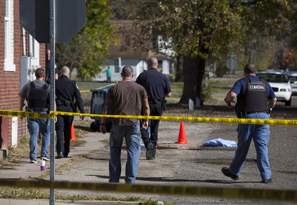 Springfield police and U.S. Marshals investigate the scene of a homicide near Eighth and Phillips streets Monday, Nov. 2, 2015. Orange cones and a blue cloth indicate where the victim was found before he was transported to the hospital. Rich Saal/The State Journal-Register