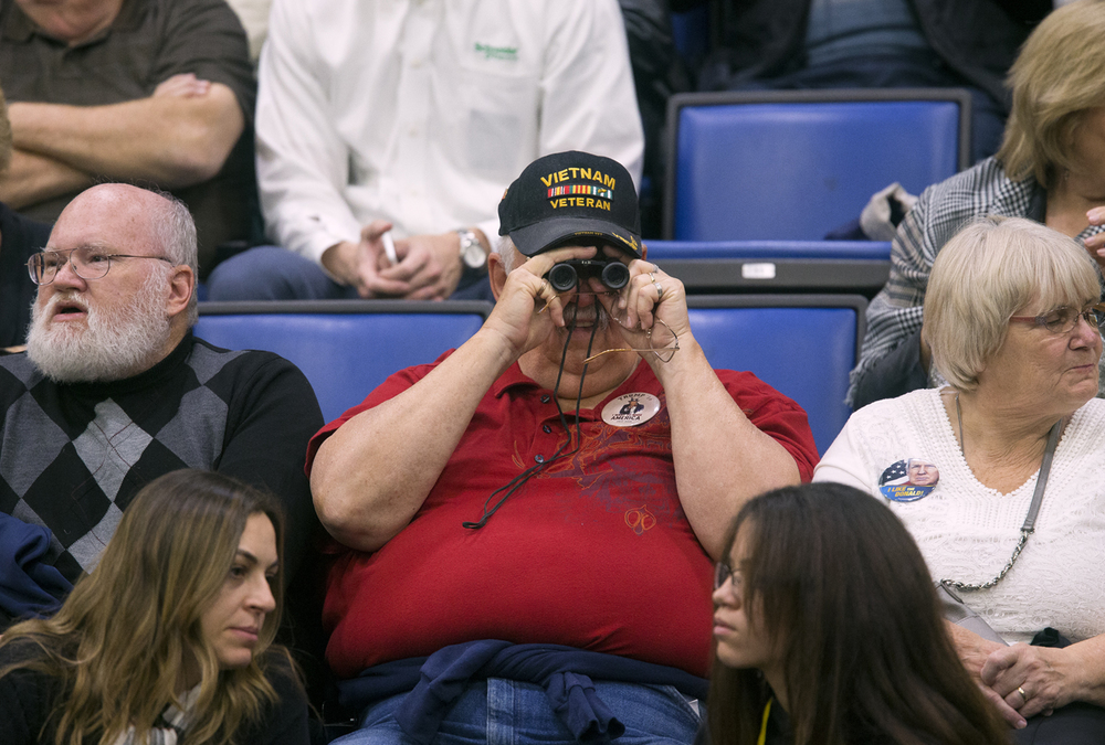 A Donald Trump supporter scans the crowd with binoculars before the Republican presidential candidate's address to a capacity crowd at the Prairie Capital Convention Center Monday, Nov. 9, 2015. Rich Saal/The State Journal-Register