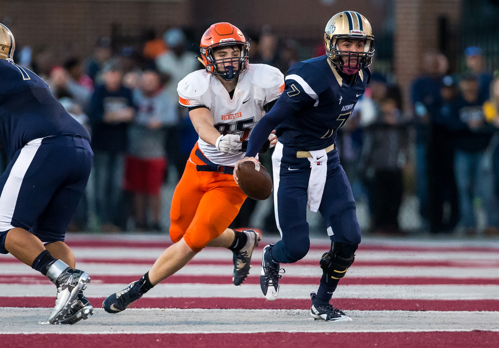 Belleville Althoff quarterback Jordan Augustine (7) escapes the grasp of Rochester's Mikey McNicholas (85) during the quarterfinal round of the Class 4A playoffs at Lindenwood University-Belleville, Saturday, Nov. 14, 2015, in Belleville , Ill. Justin L. Fowler/The State Journal-Register