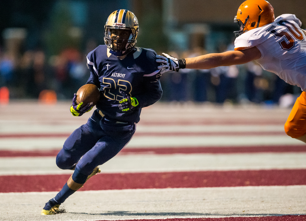 Belleville Althoff's Malik Easley (23) avoids the hand of Rochester's Brandon Jones (50) as he cuts up to gain yardage on a run in the second half during the quarterfinal round of the Class 4A playoffs at Lindenwood University-Belleville, Saturday, Nov. 14, 2015, in Belleville , Ill. Justin L. Fowler/The State Journal-Register