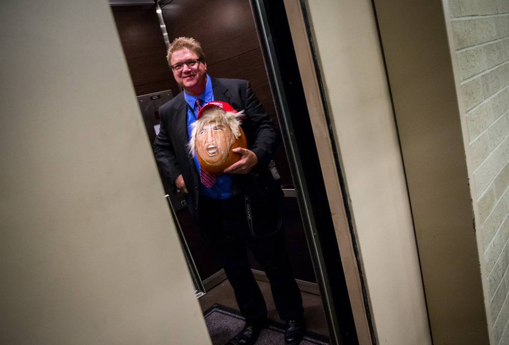 John Kettman, of La Salle, Ill., carries a pumpkin with a portrait of Republican presidential candidate Donald Trump that he painted on it while attending Trump's campaign stop at the Prairie Capital Convention Center, Monday, Nov. 9, 2015, in Springfield, Ill. Justin L. Fowler/The State Journal-Register