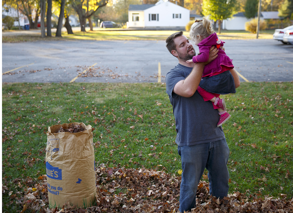 Marty Montgomery had been wrangling leaves into yard waste bags when he paused for a hug from his daughter, Kate, at the corner of Homewood Court and Filmore Street in Jerome, Tuesday, Nov. 10, 2015. Montgomery is pastor of Capital Baptist Church, which he opened at the location in September. His duties include yard work, he said. Rich Saal/The State Journal-Register