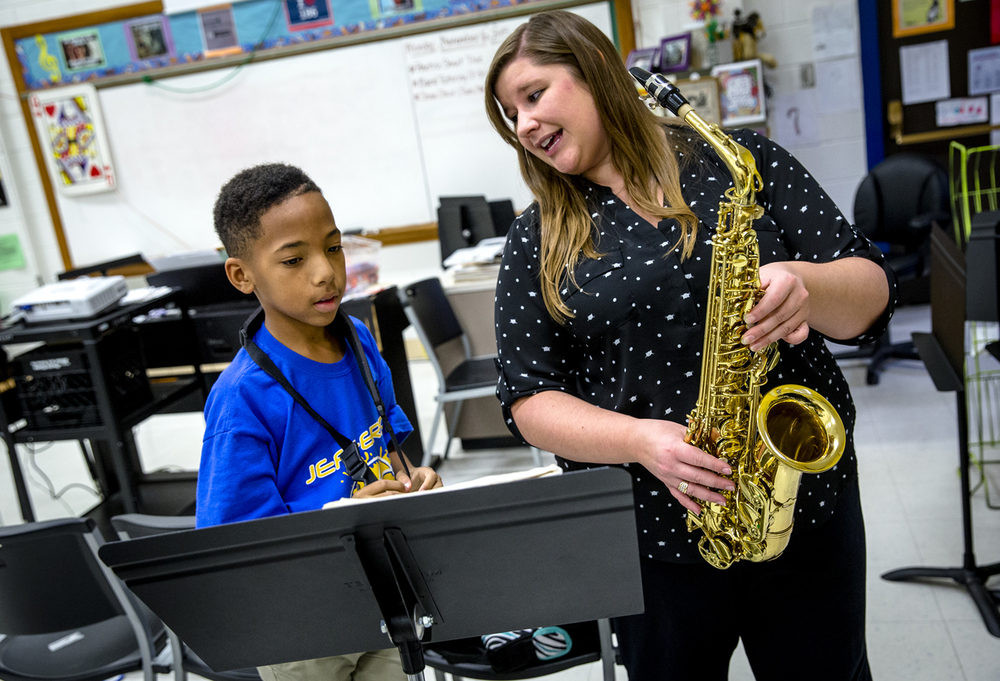 "Lacey Harrison, the choir and band director at Jefferson Middle School, helps sixth grader Amarion Santiago learn the positioning for ""Jingle Bells"" during after school band tutoring at the school, Monday, Nov. 16, 2015, in Springfield, Ill. Harrison offers the tutoring sessions once a week to help students advance their musical abilities to become self sufficient. ""I want them to have the skills that if they say, 'I don't know to play this,' they have the resources and tools to figure it out,"" said Harrison. Justin L. Fowler/The State Journal-Register"