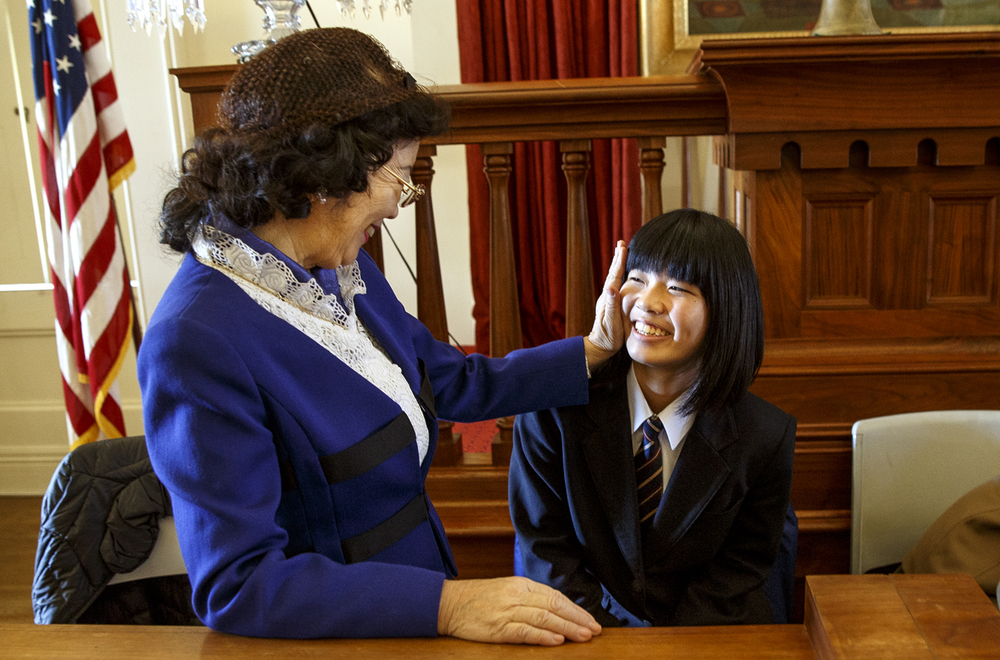 Sumiko Kunii puts her hand on Erika Kamura's cheek after she and three other students from Ashikaga, Japan recited Abraham Lincoln's Gettysburg Address to commemorate the 152nd. anniversary of the address at the Hall of Representatives at the Old State Capitol Thursday, Nov. 19, 2015. The students earned the trip to Springfield after winning a contest that involved reading the Gettysburg Address and writing an essay. Ted Schurter/The State Journal-Register
