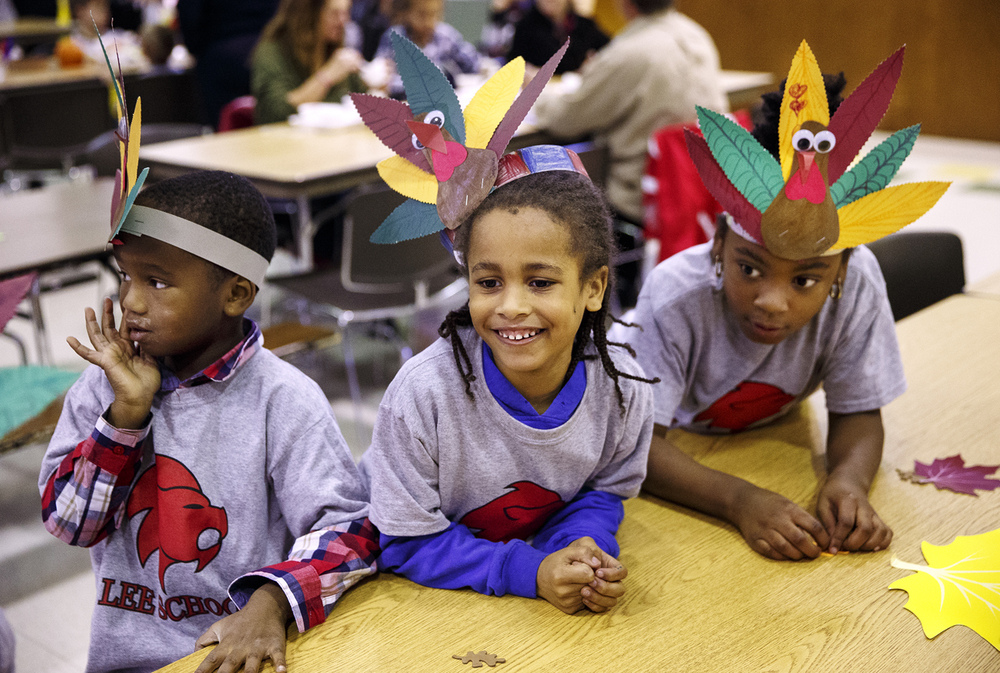 Daevon Readus, left, Jaqwan Hudson and Leziyah Hunter wear their turkey feather artwork as they sit together during the Lee School annual Thanksgiving feast Friday, Nov. 20, 2015. The school encouraged parents to participate in an academic lesson with their child and then enjoy lunch together, a school tradition for the past 15 years. Ted Schurter/The State Journal-Register